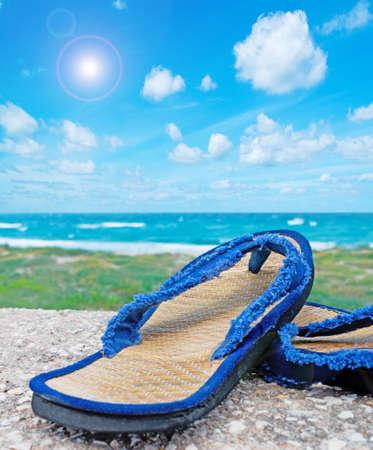 wicker flip flop on cement floor by the sea photo
