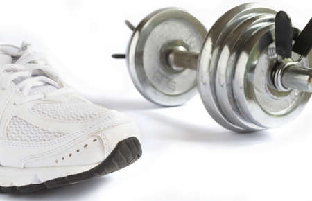 running shoe and metal dumbbell on white background photo