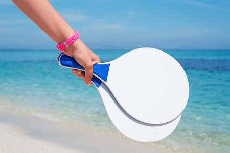 girl holding a white beach racket