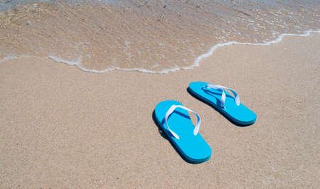 blue flip-flops on the shore Stock Photo