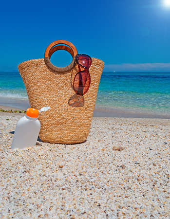 straw bag and suntan lotion under a bright sun photo