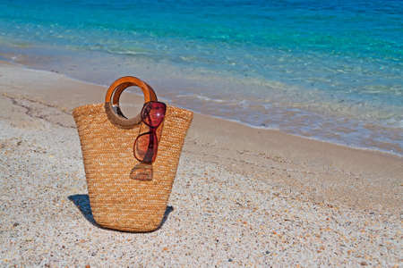 straw bag and sunglasses by the sea