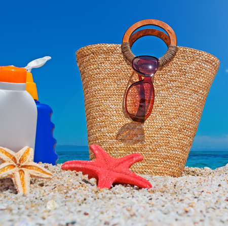 suntan lotion and straw bag at the beach photo