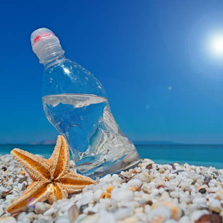 bottle of water and sea star on white pebbles under a shining sun photo