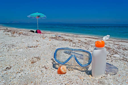 dive mask and suntan lotion at the beach photo