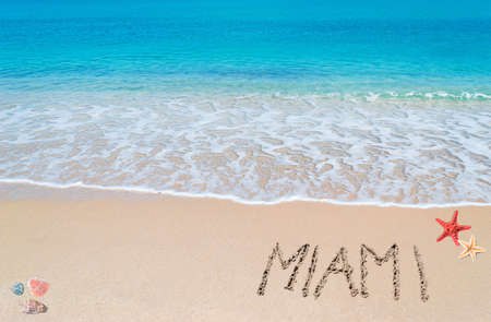 turquoise water and golden sand with shells and sea stars with miami written on it photo