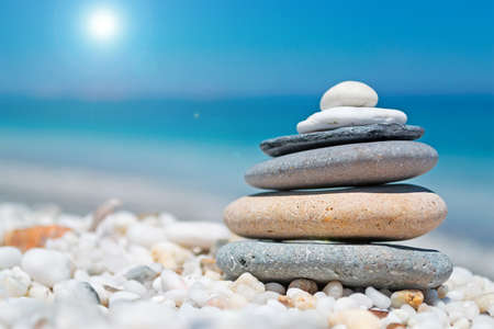 stone pile on white pebbles by the shore photo