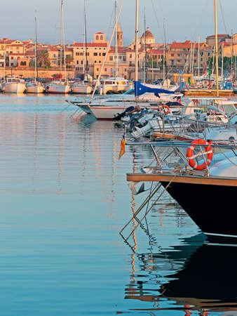 boats in Alghero harbor at dusk Stock Photo