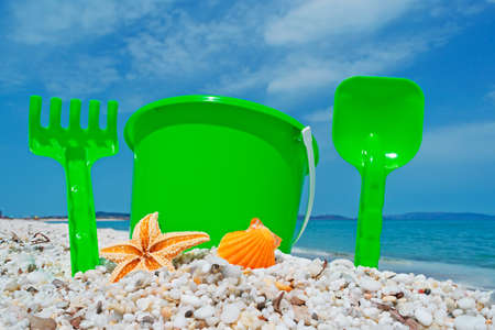 plastic scoop: green bucket, shell and starfish by the shore in Sardinia
