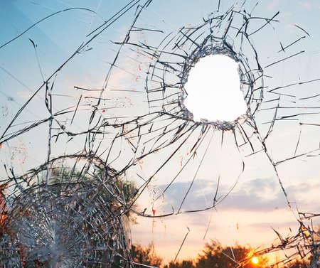 bullet hole: broken glass at sunset