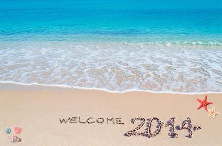 """agua turquesa y arena dorada con conchas y estrellas de mar con """"bienvenido 2014"""" escrito en �l photo"""