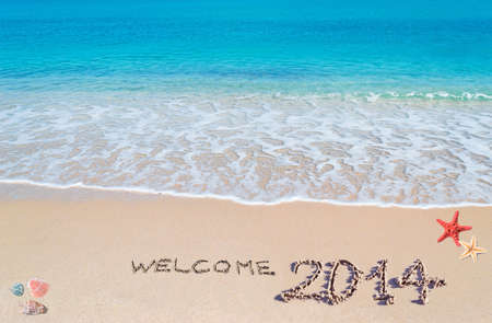 turquoise water and golden sand with shells and sea stars with welcome 2014 written on it