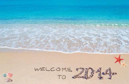 """agua turquesa y arena dorada con conchas y estrellas de mar con """"bienvenido a 2014"""" escrito en �l photo"""