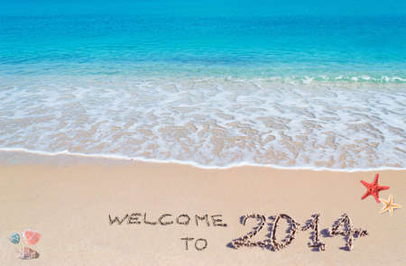 turquoise water and golden sand with shells and sea stars with welcome to 2014 written on it photo