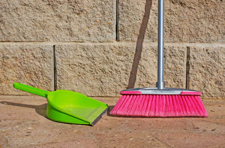 bioclean: green shovel and pink broom on the ground