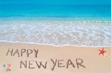 happy new year written on a tropical beach