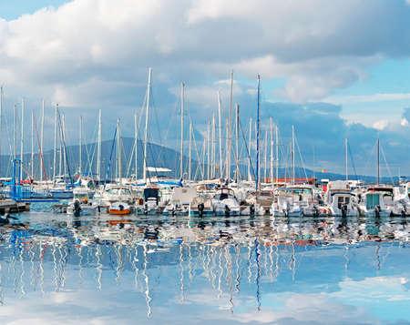 barcos en Alghero reflejan en el mar