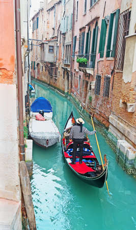 gondola with tourist in a narrow canal in Venice