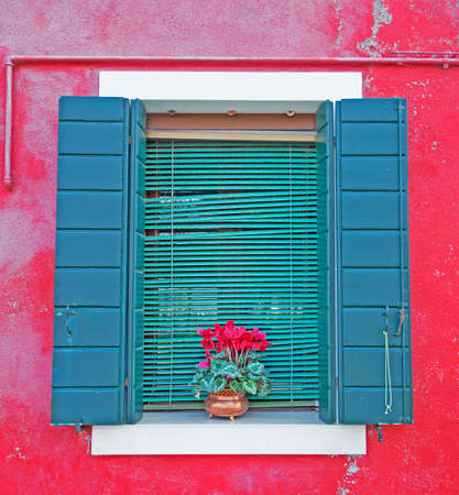green window in a red wall photo