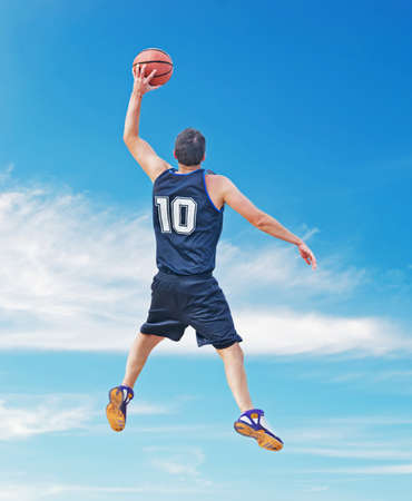 basketball player dunking in a cloudy sky