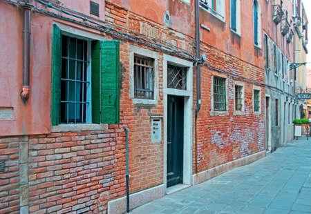 backstreet: backstreet antigua con paredes de ladrillo y una pizzer�a en Venecia, Italia Foto de archivo