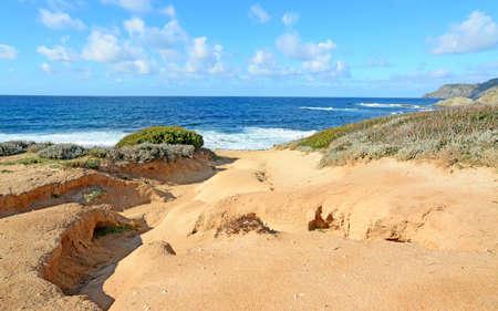 orange shore and rough sea in Argentiera, Sardinia photo