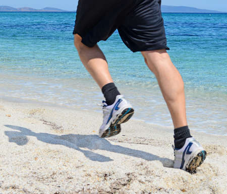 man running by a turquoise shore photo