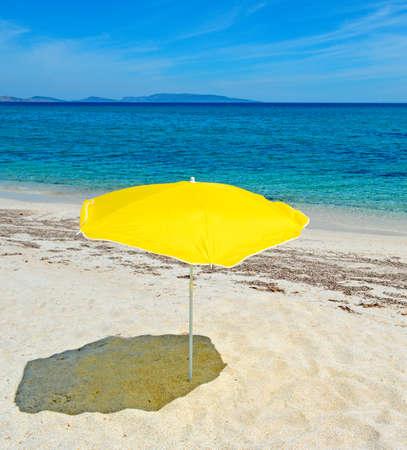 gele parasol in een verlaten strand