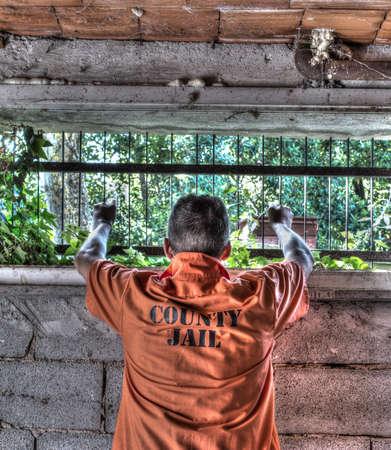 penal institution: man holding jail bars Stock Photo