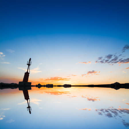 lighthouse silhouette reflected in the water photo