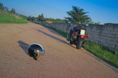motorsprot: helmet and motorcycle in an empty road at dusk