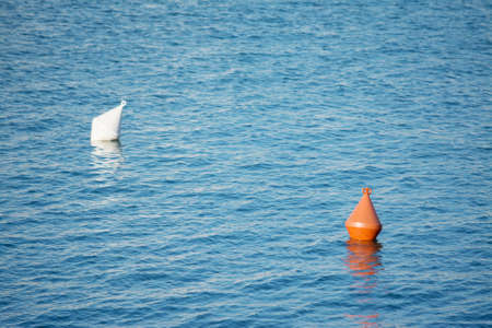 buoys: orange and white buoys floating in the sea