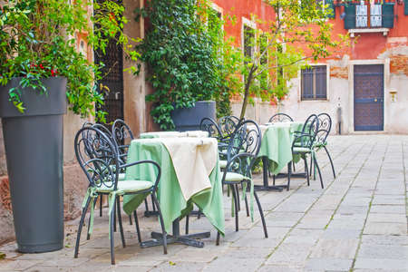 tables and chairs in a small square in Venice, Italy