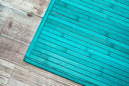 turquoise rug on a wooden floor