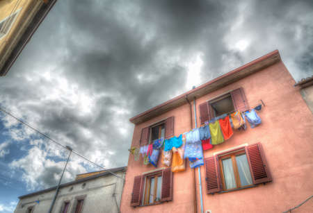 laundry line with clothes in an old building under a cloudy sky. Iso 100, heavy processed for hdr tone mapping photo
