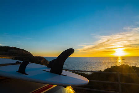surfboard fin: surfboard on a car rooftop at sunset Stock Photo