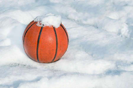 basketball on a playground covered by snow