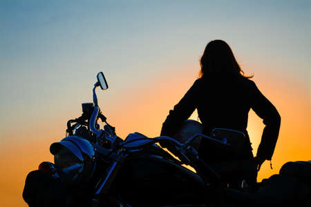classic motorcycle and girl silhouette at dusk