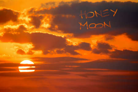 honey moon: honey moon written in the sky at sunset