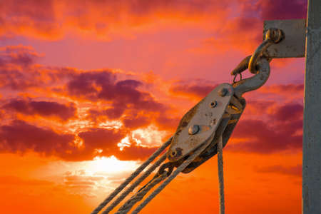 karabiner: hook with pulley under a dramatic sky at sunset. Shot in Alghero harbor, Italy