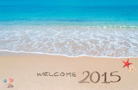 turquoise water and golden sand with shells and sea stars with welcome 2015 written on it photo