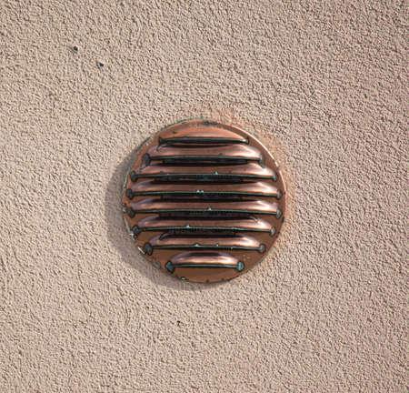 intake: air intake in a rustic wall.