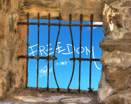 jailbreak: freedom writing seen through a jail window with bend bars