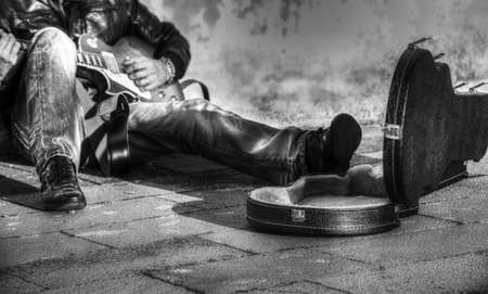 guitar player in the street with an open guitar case in black and white photo