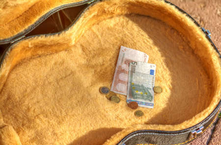 guitar case: euro bills and coins in a guitar case in the street. Hdr tone mapping effect.