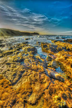 ferro: orange rocks by the shore in Porto Ferro beach, Italy