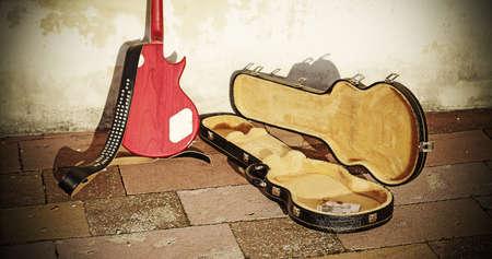 guitar case: caja de la guitarra con las monedas y billetes en el tono de la vendimia