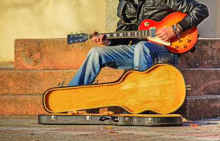 guitar player in the street with an open guitar case photo