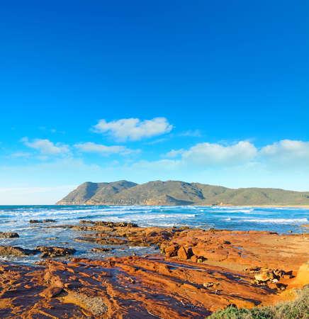 ferro: red rocks by the shore in Porto Ferro, Sardinia