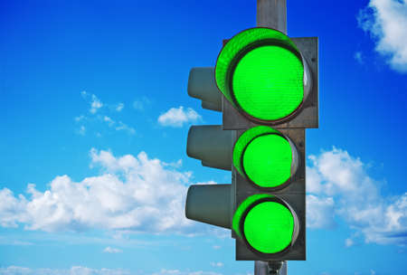 traffic light with three green lights on under a blue sky